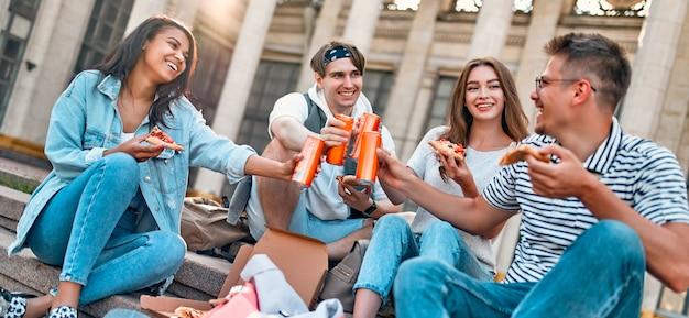 Grupa uczniów siada na schodach przed kampusem i je pizzę oraz napoje gazowane. grupa przyjaciół odpoczywa i rozmawia.