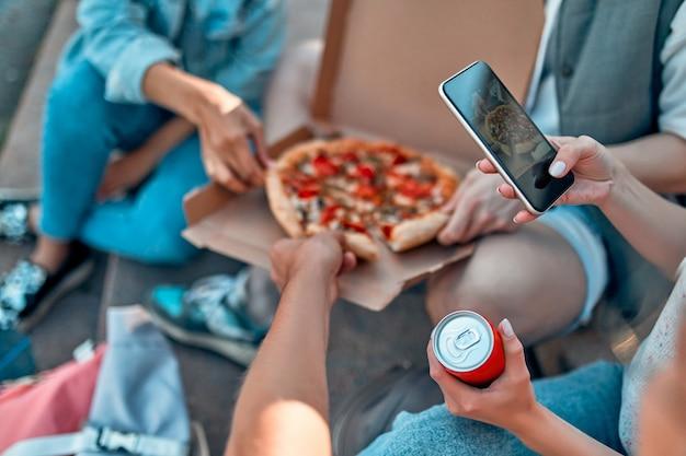 Grupa uczniów siada na schodach przed kampusem i je pizzę oraz napoje gazowane