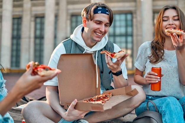 Grupa uczniów siada na schodach przed kampusem i je pizzę oraz sodę