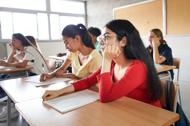 Grupa uczniów siedzących w klasie, uczęszczających do nauczyciela