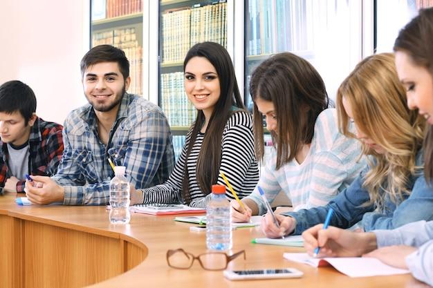 Grupa uczniów siedzi przy stole w bibliotece