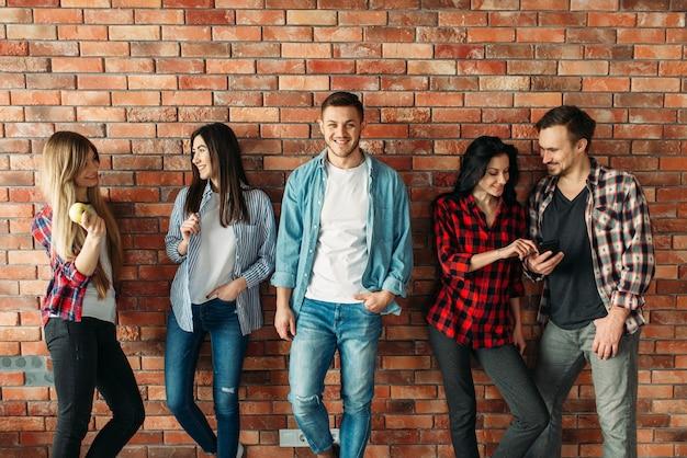 Grupa uczniów stojących przy murze z cegły