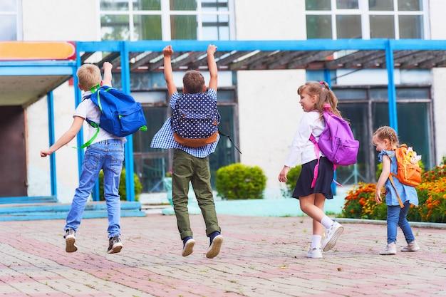 Grupa uczniów szczęśliwie skacze po szkole.
