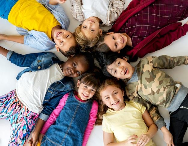 Grupa uczniów szkół podstawowych leżących na ziemi i uśmiechniętych