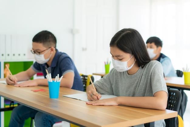Grupa uczniów szkoły podstawowej noszących maskę higieniczną w klasie