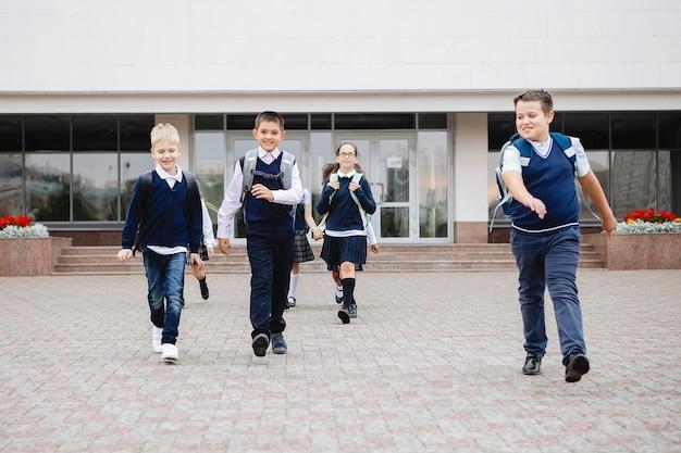 Grupa uczniów w mundurkach radośnie i wesoło wybiegła ze szkoły.