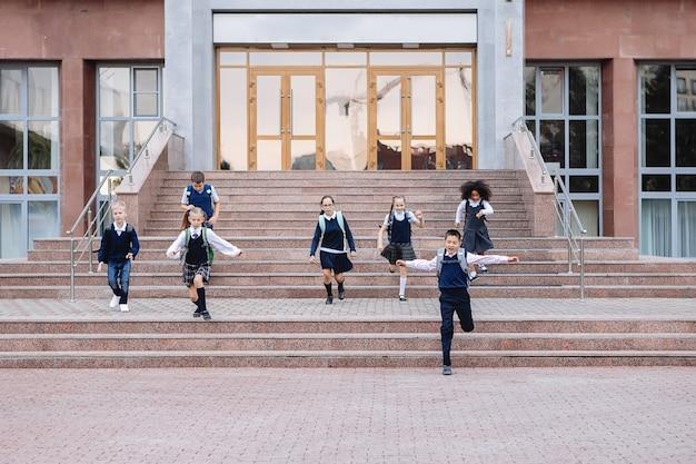 Grupa uczniów w mundurkach zbiega po schodach ze szkoły.