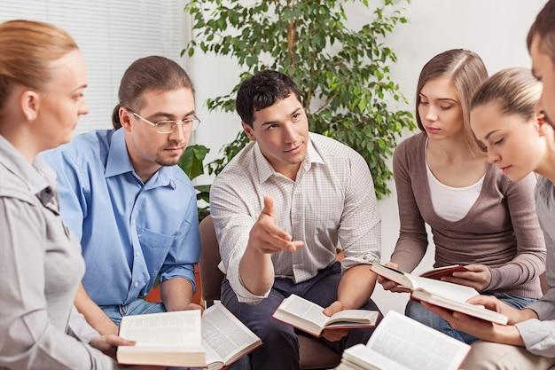 Grupa uczniów z książkami omawiająca problem