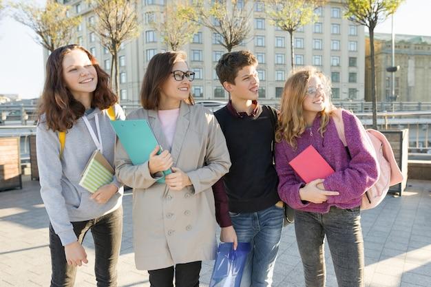 Grupa uczniów z nauczycielem, nastolatki rozmawiają z nauczycielką