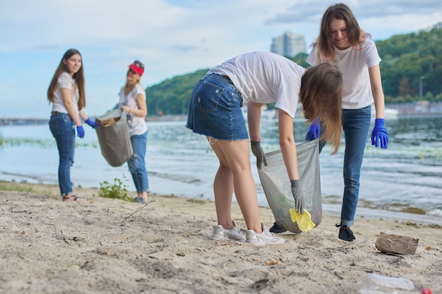 Grupa uczniów z nauczycielem w przyrodzie robi czyszczenie plastikowych śmieci. koncepcja ochrony środowiska, młodzieży, wolontariatu, dobroczynności i ekologii