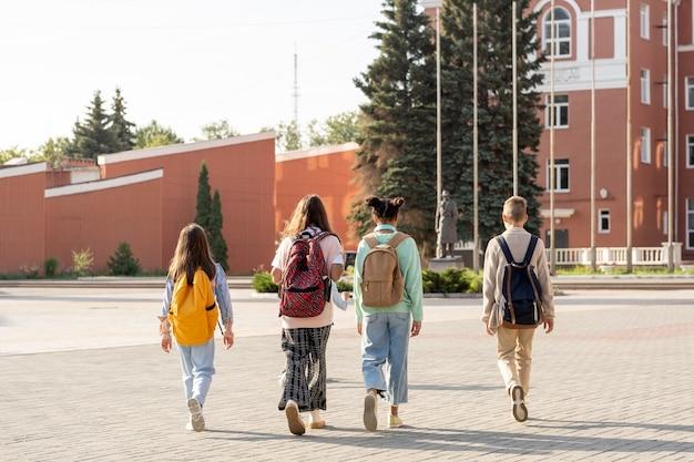 Grupa uczniów z plecakami chodzącymi rano do szkoły
