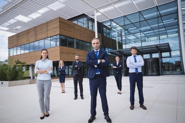 Grupa ufni biznesmeni stoi na zewnątrz budynku biurowego