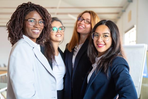 Grupa ufni młodzi bizneswomany patrzeje kamerę