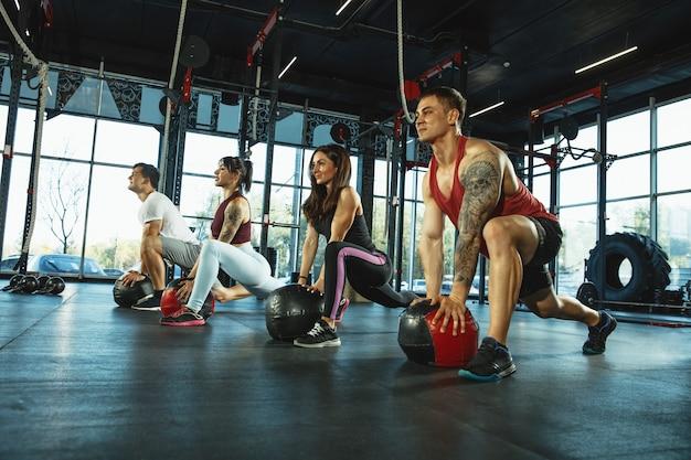 Grupa umięśnionych sportowców ćwiczących na siłowni gimnastyka treningowa fitness