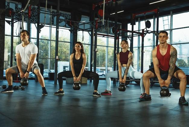 Grupa umięśnionych sportowców ćwiczących na siłowni trening gimnastyczny trening fitness