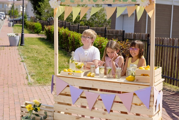 Grupa uroczych małych dziewczynek i chłopców stojących przy drewnianym straganie i sprzedających świeżą fajną domową lemoniadę w gorący letni dzień