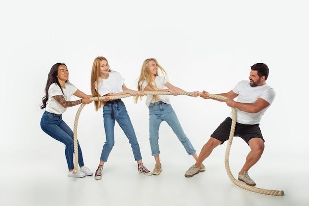 Grupa uroczych przyjaciół wieloetnicznych, zabawy na białym tle nad białym studio