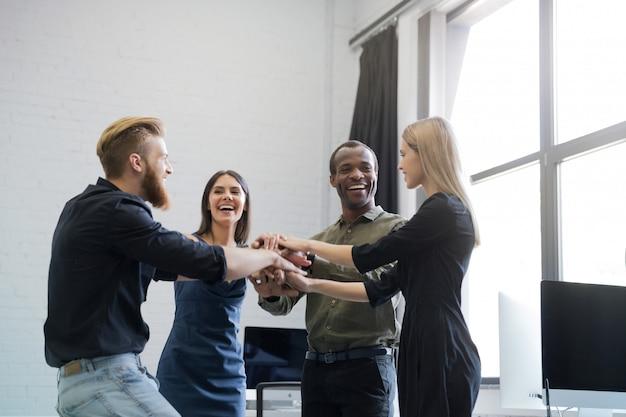 Grupa uśmiechnięci koledzy trzyma ręki