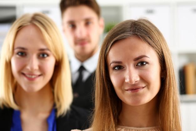 Grupa uśmiechnięci ludzie stoją w biurze patrzeje w kamerze