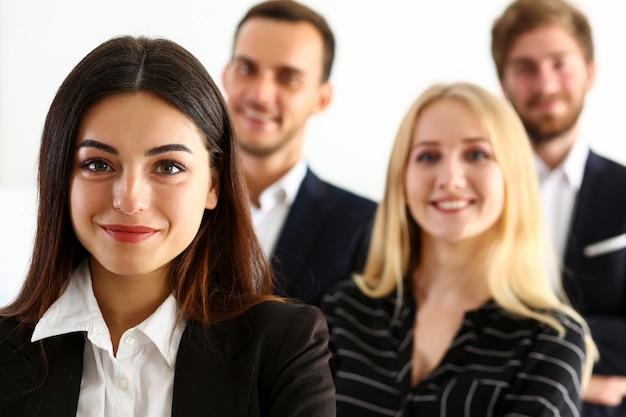 Grupa uśmiechnięci ludzie stoją w biurze