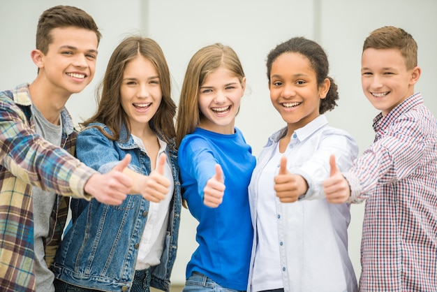 Grupa uśmiechnięci rozochoceni nastolatkowie ma zabawę po lekcji