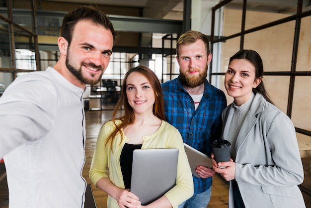 Grupa uśmiechnięci szczęśliwi młodzi biznesmeni
