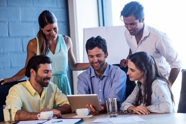 Grupa uśmiechnięci współpracownicy używa laptop