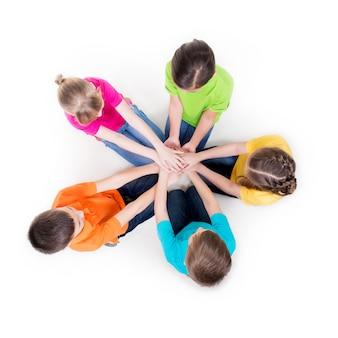 Grupa uśmiechnięte dzieci siedzą na podłodze w kręgu trzymając się za ręce - na białym tle.