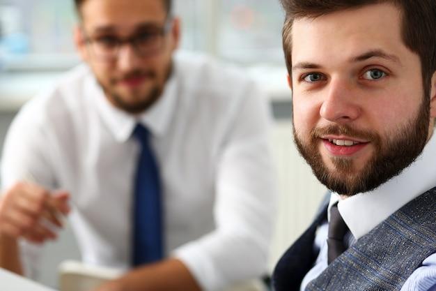 Grupa uśmiechniętych brodatych biznesmenów w garniturze i pod krawatem