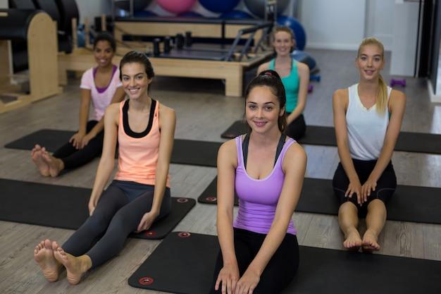 Grupa uśmiechniętych kobiet wykonujących ćwiczenia rozciągające