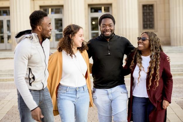 Grupa uśmiechniętych ludzi w świetle słonecznym z budynku na rozmazane