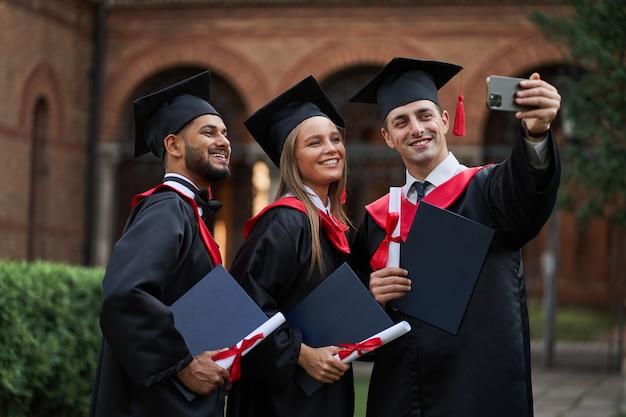 Grupa uśmiechniętych międzynarodowych absolwentów w sukniach dyplomowych robi selfie z dyplomem w kampusie
