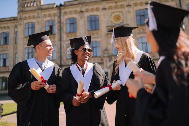 Grupa uśmiechniętych młodych ludzi stojących razem w kampusie po uzyskaniu tytułu magistra