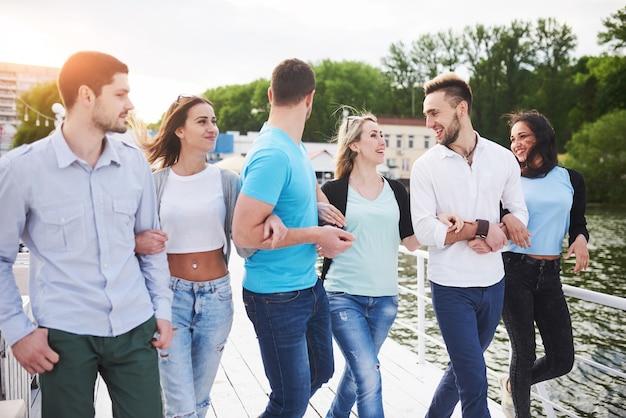 Grupa uśmiechniętych młodych ludzi sukcesu na wakacjach na stacji dokującej.
