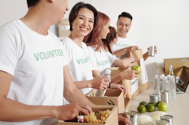 Grupa uśmiechniętych młodych studentów wolontariatu w biurze fundacji charytatywnej i pakowania żywności i wody w duże papierowe paczki dla potrzebujących