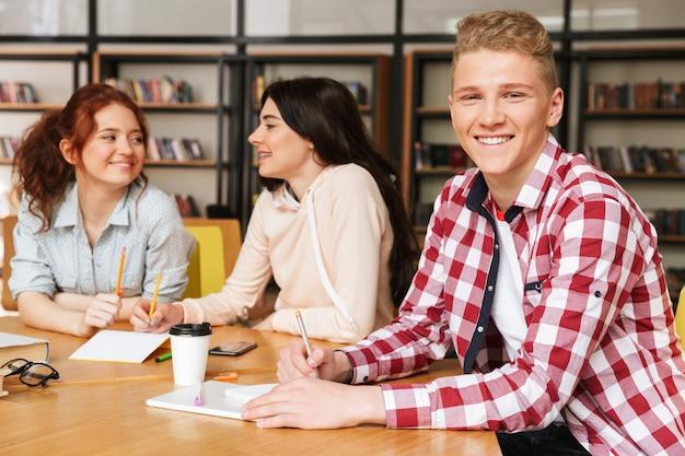 Grupa uśmiechniętych nastolatków odrabiania lekcji