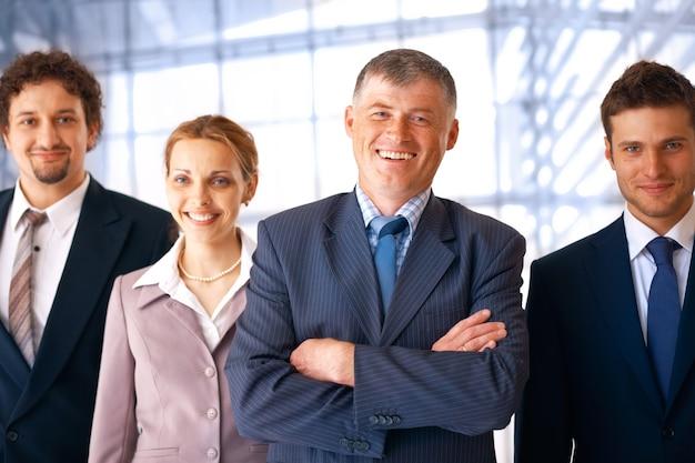 Grupa uśmiechniętych pewnych siebie ludzi biznesu ze swoim liderem w biurze.