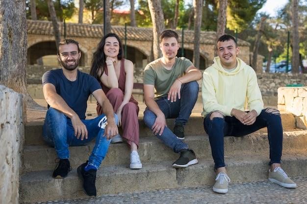 Grupa uśmiechniętych przyjaciół siedzących na schodach parku patrzą w kamerę