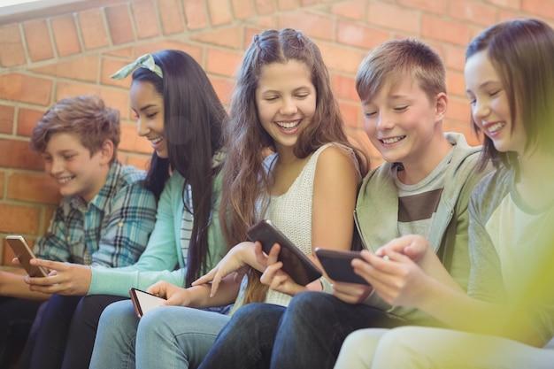 Grupa uśmiechniętych przyjaciół szkoły siedzi na schodach przy użyciu telefonu komórkowego