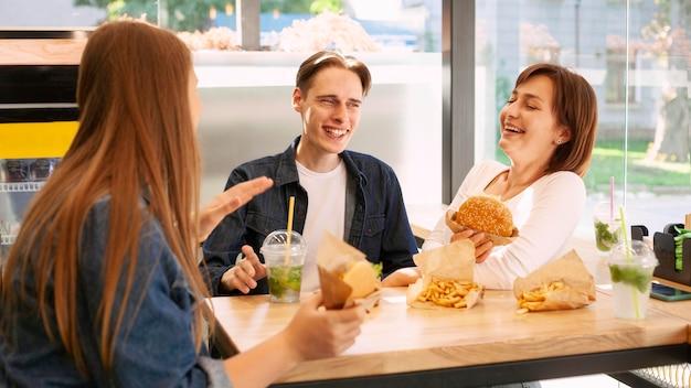 Grupa uśmiechniętych przyjaciół w restauracji typu fast food