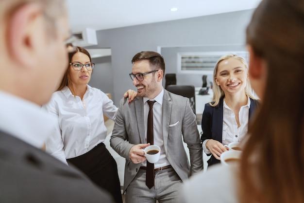 Grupa uśmiechniętych wesołych kolegów siedzących i stojących w miejscu pracy, rozmawiających i pijących kawę na pauzę.