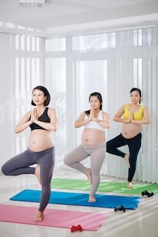 Grupa uśmiechniętych wietnamskich kobiet w ciąży stojących w pozycji drzewa podczas zajęć jogi