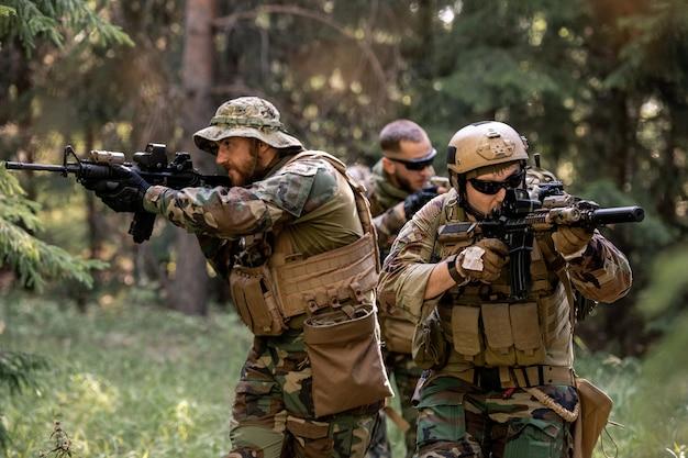 Grupa uważnych uzbrojonych żołnierzy w kamuflażach poruszających się z karabinami w lesie podczas prac porządkowych