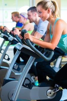 Grupa w siłowni przędzenia na rowerze sportowym