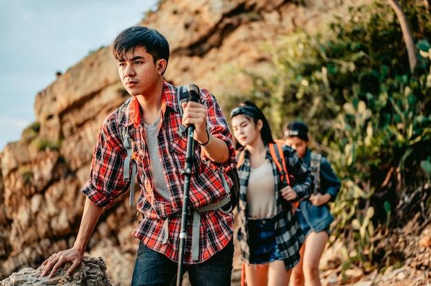 Grupa wędrowców przemierza skały, korzystając z kijków trekkingowych, aby ich wesprzećpodróż i przygoda