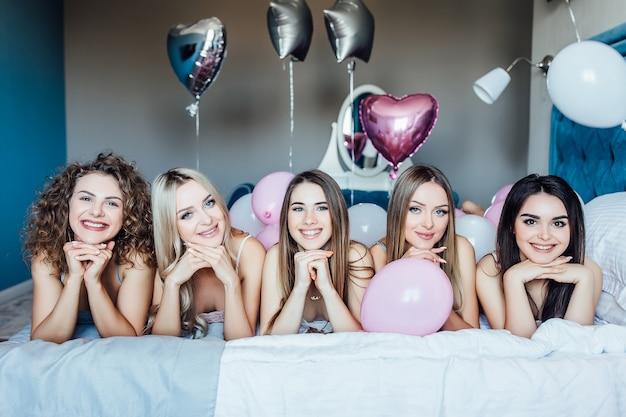 Grupa wesołej pięknej kobiety leżącej na łóżku