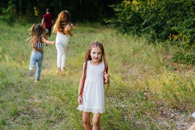 Grupa wesołych dzieci biega i bawi się w parku o zachodzie słońca. letni obóz dla dzieci.