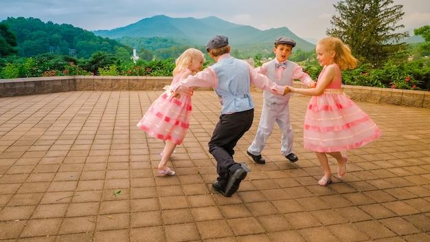 Grupa wesołych dzieciaków bawiących się i tańczących razem na terenie otoczonym piękną zielenią