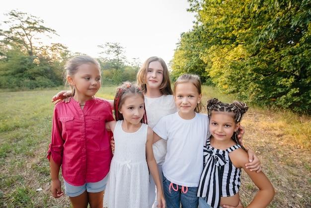 Grupa wesołych dziewczyn uśmiecha się i bawi się w parku podczas zachodu słońca. letni obóz dla dzieci.
