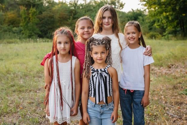 Grupa wesołych dziewczyn uśmiecha się i bawi się w parku podczas zachodu słońca